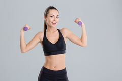 Happy beautiful young fitness woman working out with dumbbells Royalty Free Stock Image
