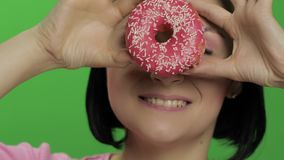 Happy beautiful young girl posing and having fun with donut. Chroma key. Happy beautiful young girl on a chroma key background having fun with donut. Cute woman stock video