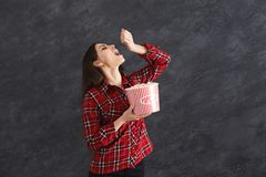 Happy beautiful young girl eating popcorns on grey background. Happy beautiful young girl eating popcorn, while watching film on grey background Royalty Free Stock Images