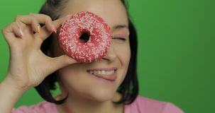 Happy beautiful young girl posing and having fun with donuts. Chroma key royalty free stock photo
