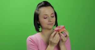 Happy beautiful young girl posing and wants to eat a donut. Chroma key. Happy beautiful young girl on a chroma key background wants to eat a donut. Cute woman in stock footage