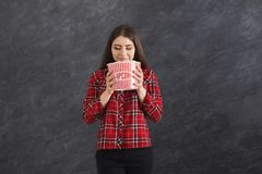 Happy beautiful young girl smelling popcorns on grey background. Happy beautiful young girl smelling popcorn with closed eyes, while watching film on grey Royalty Free Stock Images