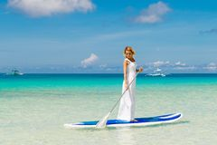 Happy beautiful young girl in a white dress with paddle board on. A tropical beach. Blue sea in the background. Summer vacation concept stock images