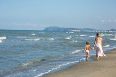 Happy beautiful young mom and child walking along the sea beach, waves and wind Royalty Free Stock Images