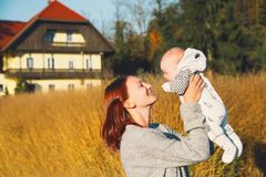 Happy beautiful young mother with her baby child on nature. Stock Photo