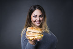 Happy beautiful young plus size model posing with hamburger on a gray studio background, xxl woman eating burger Royalty Free Stock Photography