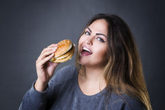 Happy beautiful young plus size model posing with hamburger on a gray studio background, xxl woman eating burger Royalty Free Stock Photo