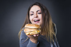 Happy beautiful young plus size model posing with hamburger on a gray studio background, xxl woman eating burger Stock Photo