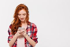 Happy beautiful young redhead lady chatting by mobile phone. Image of happy beautiful young redhead lady standing isolated over white wall background. Looking Royalty Free Stock Photo