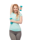 Happy beautiful young sporty woman with dumbbells Royalty Free Stock Photos