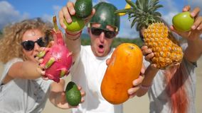 Happy beautiful young vegan friends having silly fun on the beach and dancing with exotic thai fruits. Phangan, Thailand