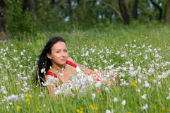 Happy beautiful young woman. In green summer flowers field royalty free stock photos