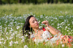 Happy beautiful young woman. In green summer flowers field royalty free stock photo