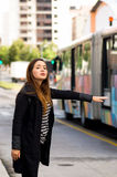 Happy beautiful young woman asking for a taxi on the street with a blurred bus behind, city background Royalty Free Stock Photography