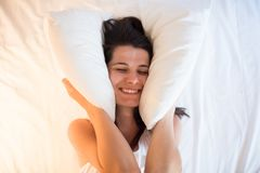 Happy beautiful young woman awake in the morning, clutching a pi. Llow to the face. View from above Royalty Free Stock Photos