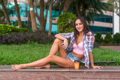 Happy beautiful young woman with bare legs sitting on stone curb in the park and listening to music in headphones. Royalty Free Stock Photos