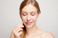 Happy beautiful young woman cleaning skin by cotton swab. stock images