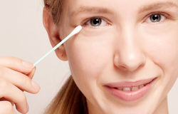 Happy beautiful young woman cleaning skin by cotton swab. Stock Image
