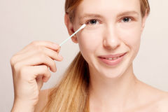 Happy beautiful young woman cleaning skin by cotton swab. Stock Photography