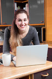 Happy beautiful young woman with computer to telecommute from home royalty free stock images