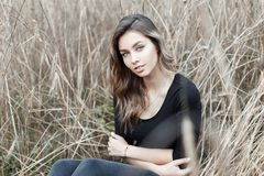 Happy beautiful young woman with a cute smile in a fashionable shirt in stylish jeans is sitting in the dry autumn grass outdoors stock photos