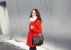 Happy beautiful young woman dressed a red jacket with black bag Stock Photos