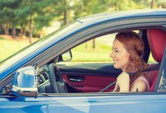 Happy beautiful young woman driving her new blue car Stock Photos