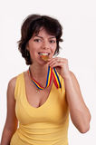 Happy beautiful young woman with gold medal between her teeth trying metal Stock Photography