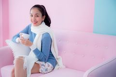 Happy beautiful young woman holding coffee cup wearing scarf sitting on living room pastel color tone. The happy beautiful young woman holding coffee cup Royalty Free Stock Photography