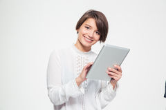 Happy beautiful young woman holding and using tablet Stock Photography