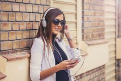 Happy beautiful young woman listening to music via headphones. On the street on a sunny day.  Brick Wall Background Stock Photography