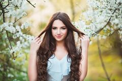 Happy beautiful young woman with long black healthy hair enjoy fresh flowers and sun light in blossom park at sunset. Happy beautiful young woman with long Stock Images