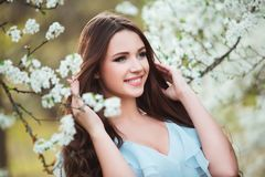 Happy beautiful young woman with long black healthy hair enjoy fresh flowers and sun light in blossom park at sunset. Happy beautiful young woman with long Royalty Free Stock Images