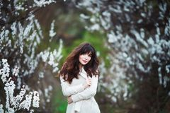 Happy beautiful young woman with long black healthy hair enjoy fresh flowers and sun light in blossom park at sunset. Happy beautiful young woman with long Stock Photos