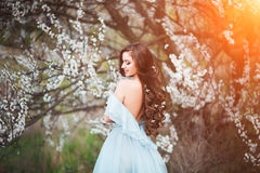 Happy beautiful young woman with long black healthy hair enjoy fresh flowers and sun light in blossom park at sunset. Happy beautiful young woman with long Royalty Free Stock Photos