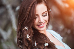 Happy beautiful young woman with long black healthy hair enjoy fresh flowers and sun light in blossom park at sunset. Stock Image