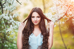 Happy beautiful young woman with long black healthy hair enjoy fresh flowers and sun light in blossom park at sunset. Stock Images