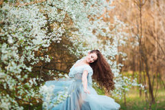 Happy beautiful young woman with long black healthy hair enjoy fresh flowers and sun light in blossom park at sunset. Royalty Free Stock Photo