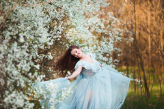 Happy beautiful young woman with long black healthy hair enjoy fresh flowers and sun light in blossom park at sunset. Royalty Free Stock Images