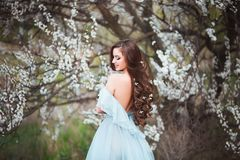 Happy beautiful young woman with long black healthy hair enjoy fresh flowers and sun light in blossom park at sunset. Happy beautiful young woman with long Royalty Free Stock Image