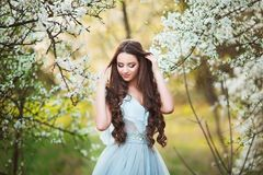 Happy beautiful young woman with long black healthy hair enjoy fresh flowers and sun light in blossom park at sunset. Happy beautiful young woman with long Royalty Free Stock Photography
