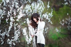 Happy beautiful young woman with long black healthy hair enjoy fresh flowers and sun light in blossom park at sunset. Happy beautiful young woman with long Stock Photo