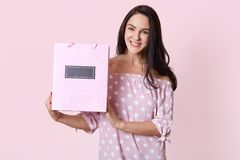 Happy beautiful young woman in polka dot dress, holding shopping bags in her hands and smiling happily. Studio shot of happy stock images