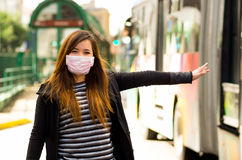 Happy beautiful young woman with protective mask on the street in the city with air pollution, asking for a taxi with a Stock Photo