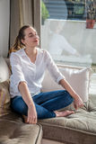 Happy beautiful young woman relaxing in yoga lotus position Stock Photo