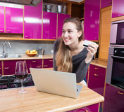 Happy beautiful young woman shopping online, thinking about future purchase. Using her laptop and credit card for mobile commerce from her home kitchen with a Royalty Free Stock Image