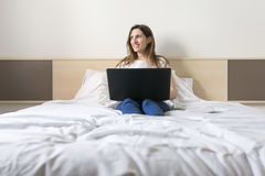 Happy beautiful young woman sitting on bed using laptop at home. Royalty Free Stock Image