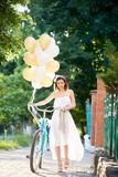 Happy woman holding baloons while riding bicycle. Happy beautiful young woman smiling walking in the park with her bicycle and bunch of colored baloons in her Royalty Free Stock Photography