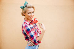 Happy beautiful young woman standing and eating sweet lollipop Royalty Free Stock Photo