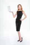 Happy beautiful young woman standing and holding laptop. Full length of happy beautiful young businesswoman standing and holding laptop over white background stock photo